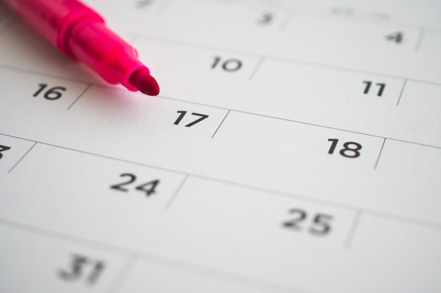 Strona kalendarza z czerwonym piórem z bliska