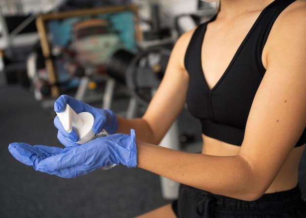 Strona kobiety w rękawiczkach za pomocą środka dezynfekującego do rąk na siłowni