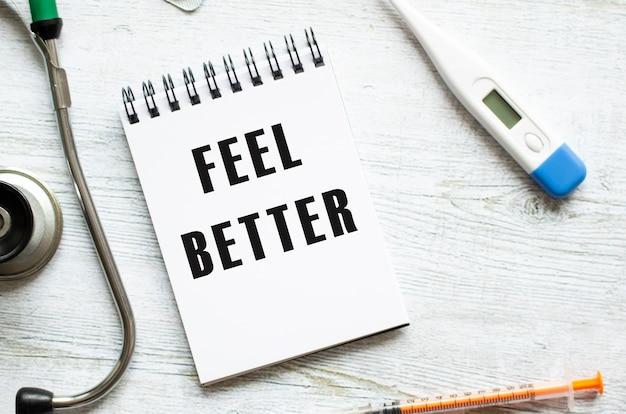 Strona notesu z tekstem poczuj się lepiej na stole ze stetoskopem