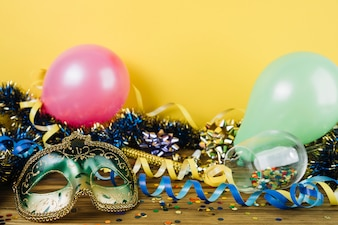 Strona ozdoba materiału z maskarada maski karnawał pióro i balony na drewnianym stole