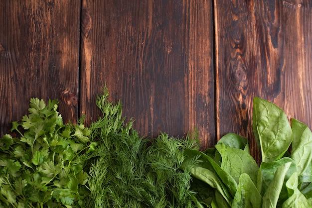 Strona pęczki zieleni: szpinak, koperek, kolendra, pietruszka na drewnianym tle, miejsce, koncepcja surowej żywności, z bliska.
