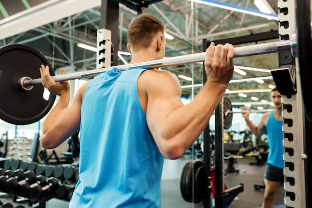 Strong man lifting barbell in gym
