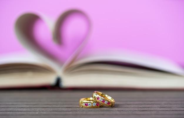 Strony książki o zakrzywionym kształcie serca i pierścieniu pielącym