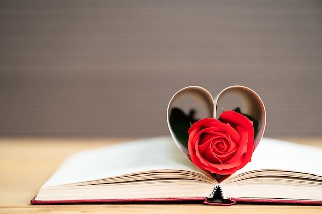 Strony książki o zakrzywionym kształcie serca z czerwoną różą