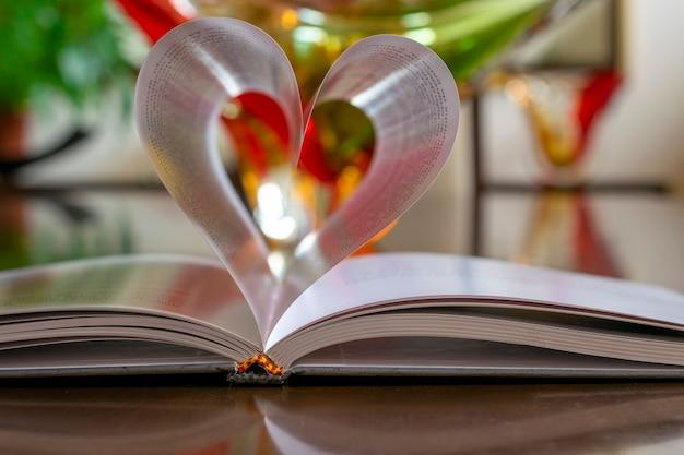 Strony książki w kształcie serca z rozmytym tłem. selektywne skupienie.