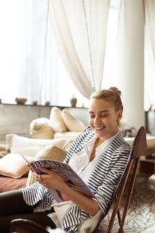 Strony magazynu. roześmiana, atrakcyjna kobieta o szerokim uśmiechu, zainteresowana informacjami z magazynu kosmetycznego