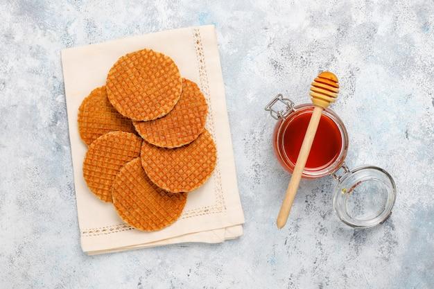 Stroopwafels, karmelowe holenderskie gofry z herbatą lub kawą i miodem na betonie