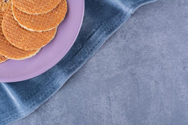Stroopwafels na białym tle w fioletowym talerzu na kamieniu.