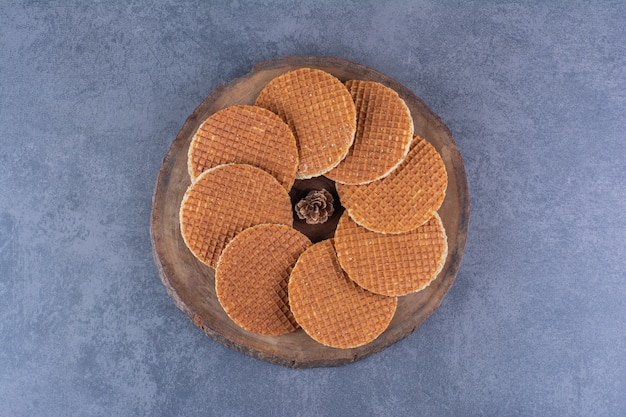 Stroopwafels z szyszką na białym tle w drewnianej tablicy na kamieniu. zdjęcie wysokiej jakości