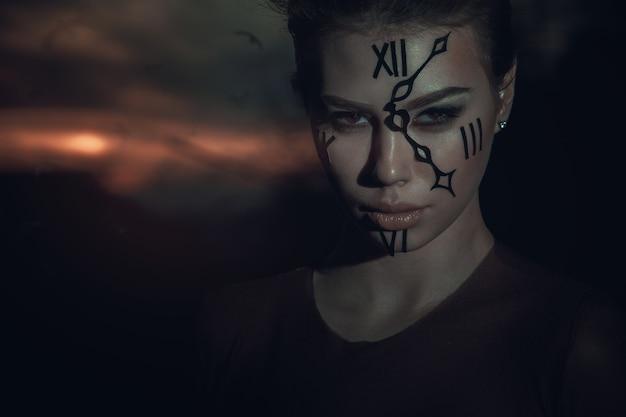 Stróż. strażnik czasu. kobieta z zegarkiem na twarzy o zachodzie słońca. dramatyczny obraz.