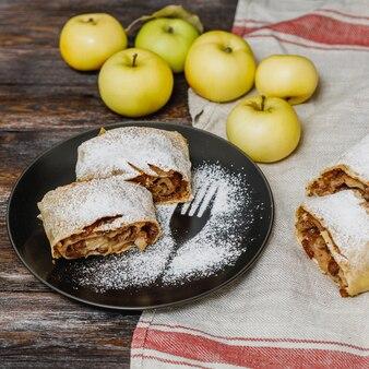 Strudel jabłkowy w czarnej płycie na podłoże drewniane