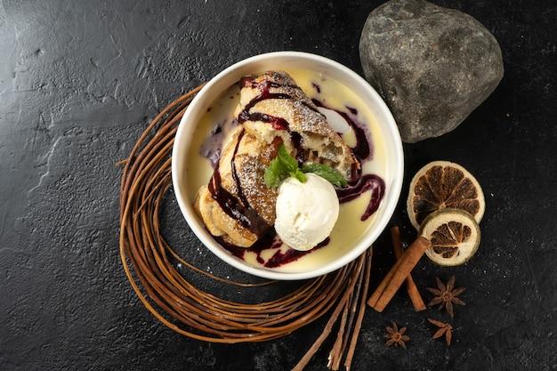 Strudel z lodami. klasyczny słodki deser z sosem jagodowym i gałką lodów waniliowych