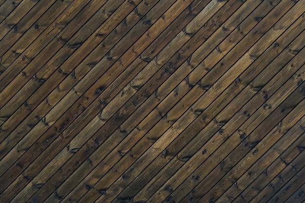 Struktura drewna tło ciemnobrązowy kolor 45 stopni. tekstura starych drewnianych desek pod kątem ukośnym.