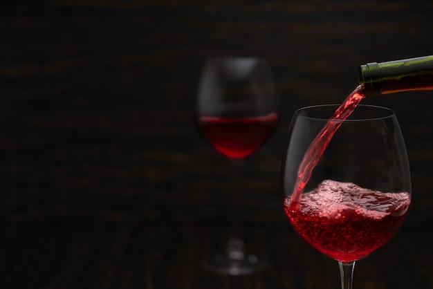 Strumień czerwonego wina przelewa się do szklanek z bliska, plusk.