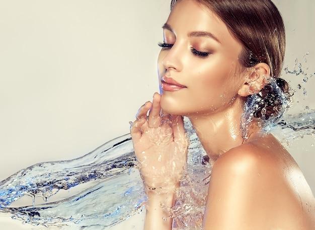 Strumień czystej błękitnej wody dotyka dłoni, szyi i ciała młodej atrakcyjnej kobiety