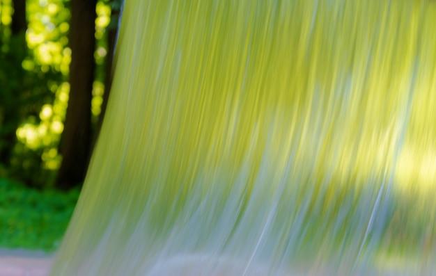 Strumień płynącej wody na tle lasu.