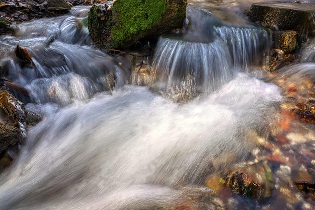 Strumień płynący czystą źródlaną wodą. zdjęcie zrobione jesienią w rosji.