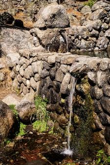 Strumień świeżej wody wychodzącej z metalowej wylewki z fontanny