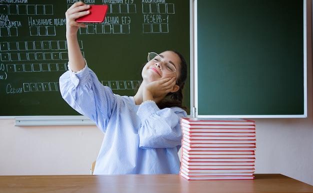 Strumień vlogger online. uczeń jest usytuowanym przeciw blackboard z telefonem