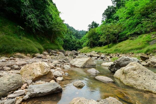 Strumień wody płynący w środku kanionu głazów.