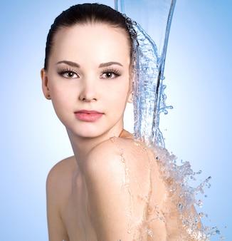 Strumień wody spada na młodą kobietę z piękną skórą - niebieska ściana