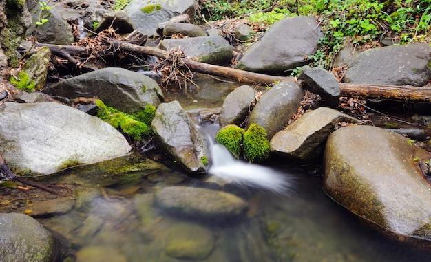 Strumień z wodospadem i omszałymi kamieniami wokół