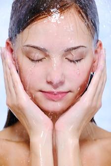 Strumienie wody na młodej pięknej kobiecej twarzy - zbliżenie
