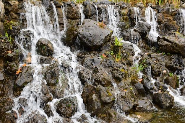 Strumienie wody płyną strumieniami po mokrych kamieniach. tło dla całej klatki.