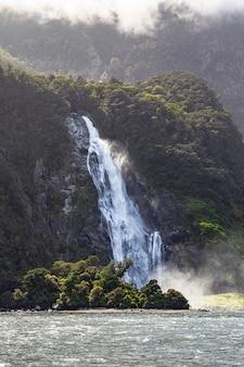 Strumienie z górskiego wodospadu na tle zielonej góry w nowej zelandii