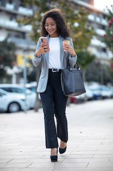 Strzał całkiem młoda kobieta biznesu za pomocą swojego inteligentnego telefonu podczas picia kawy idąc ulicą.