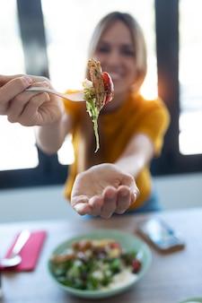 Strzał całkiem młoda kobieta pokazuje sałatkę do kamery podczas jedzenia w kuchni w domu.