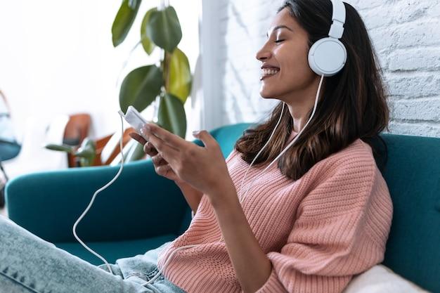 Strzał całkiem młoda kobieta słuchania muzyki z cyfrowego tabletu siedząc na kanapie w domu.