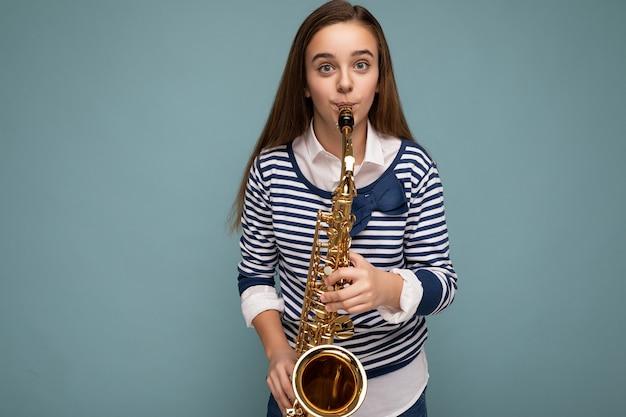Strzał całkiem pozytywny szczęśliwy brunet mała dziewczynka sobie stylowe paski longsleeve stojący na białym tle nad niebieskim tle ściany gra na instrumencie muzycznym, patrząc na kamery