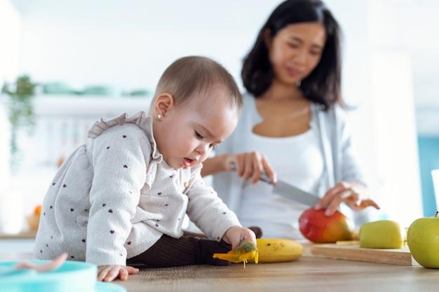Strzał cute dziewczynka bawi się jedzeniem, podczas gdy jej matka kroi owoce, aby przygotować owsiankę dla dzieci w kuchni.