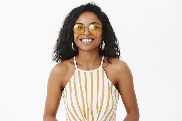 Strzał do pasa uroczej modnej afrykańskiej amerykańskiej młodej podróżniczki w słodkie żółte okulary przeciwsłoneczne