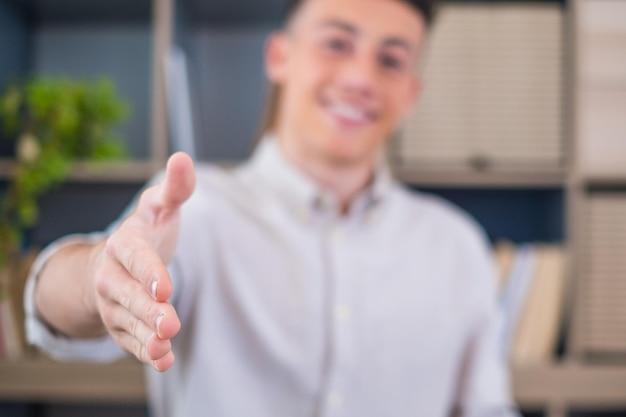 Strzał głową portret uśmiechnięty biznesmen w okularach wyciągając rękę do uścisku dłoni przed kamerą, przyjazny menedżer hr pozdrawiający kandydata na rozmowę kwalifikacyjną, oferując umowę, witając klienta na spotkaniu