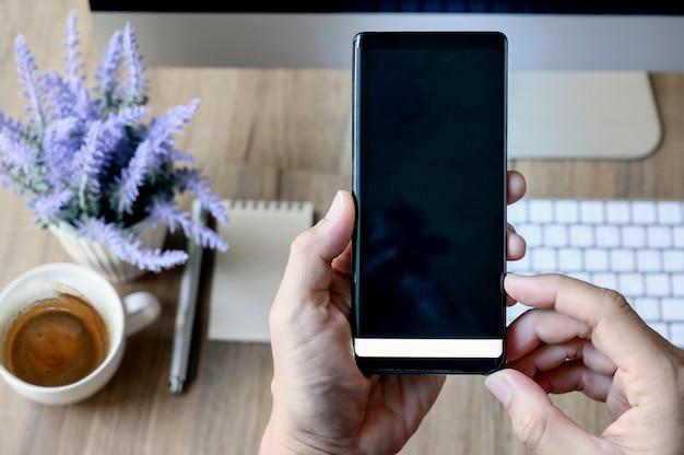 Strzał mężczyzna ręka używać mobilnego smartphone na biurowym drewnianym biurka tle.