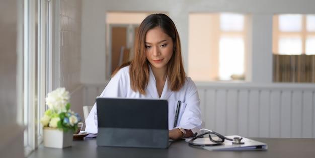 Strzał młoda kobiety lekarka pracuje na ekspertyzie medycznej z pastylką w biurowym pokoju