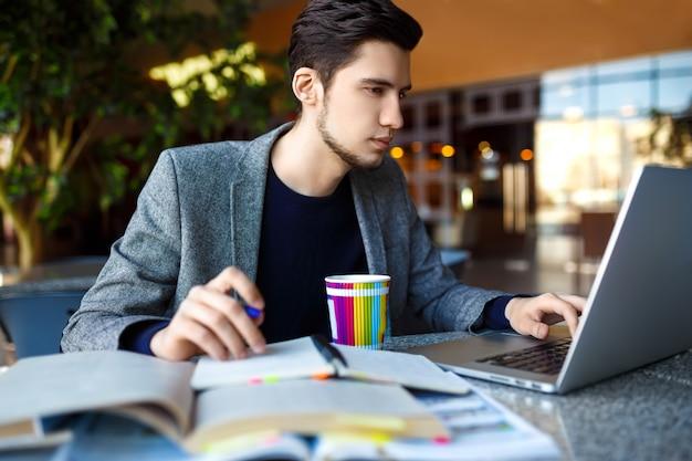 Strzał młody męskiego ucznia obsiadanie przy stołem i writing na notatniku. młody męski uczeń studiuje w kawiarni.