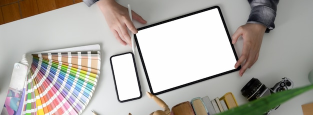Strzał ogólny kobiet projektant pracujący z pustego ekranu tabletu i smartfona