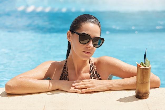 Strzał oszałamiająco piękna młoda kobieta cieszy się opalać się w basenie z świeżym owocowym koktajlem
