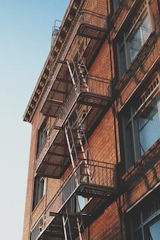 Strzał pionowy pod niskim kątem starego budynku z cegły ze schodami ewakuacyjnymi z boku