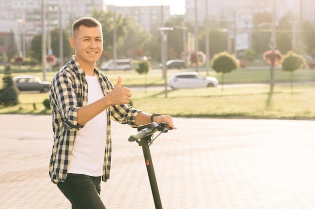 Strzał portret kaukaski hipster człowieka, opierając się na skuter elektryczny, patrząc na kamery i pokazując kciuk do góry. hipster człowiek na zewnątrz pojazdu. ekologiczny nowoczesny transport miejski