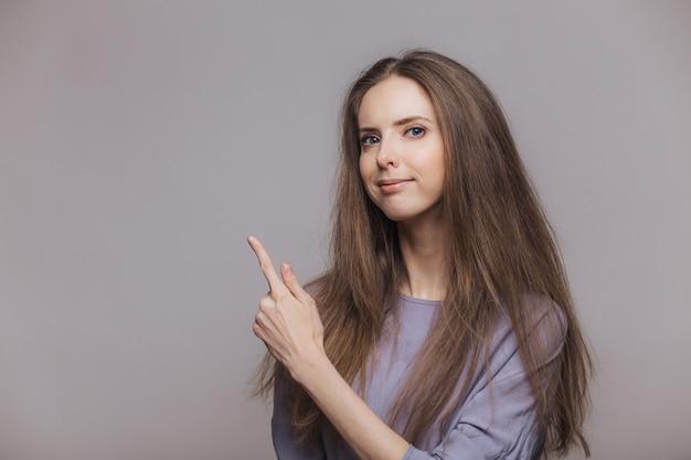 Strzał poważna przyjemnie wyglądająca brunetki kobieta o niebieskich oczach, ubrana od niechcenia, wskazuje palcem wskazującym na puste miejsce