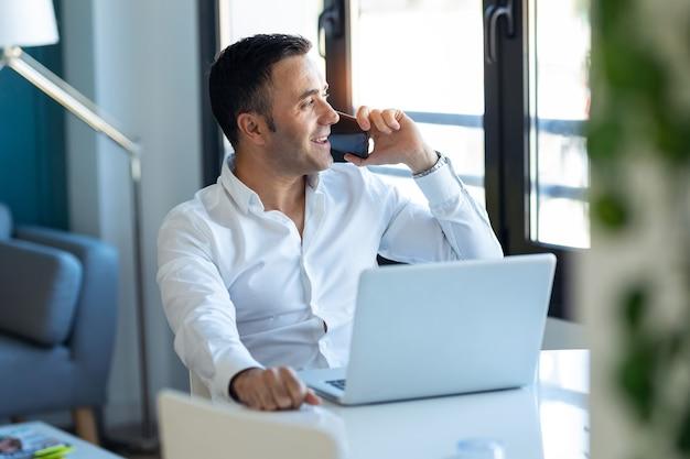 Strzał przystojny biznesmen rozmawia przez telefon komórkowy podczas pracy z laptopem w domu.