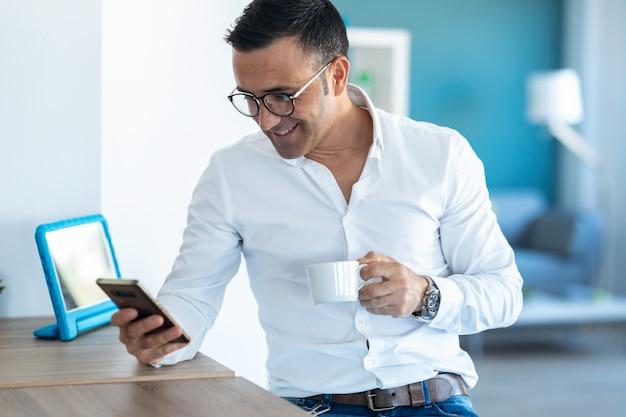 Strzał przystojny biznesmen wysyłanie wiadomości z telefonu komórkowego podczas picia kawy w domu.