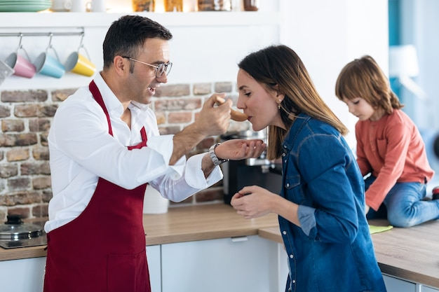 Strzał przystojny mężczyzna, gotowanie i pozwalając żonie smakować jedzenie w kuchni w domu.