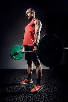 Strzał silny muskularny kulturysta lekkoatletycznego mężczyzna pompowania mięśni ze sztangą na ciemnym studio.
