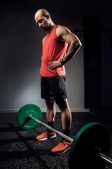 Strzał silny muskularny kulturysta lekkoatletycznego mężczyzna przygotowuje się do treningu ze sztangą na ciemnym studio.