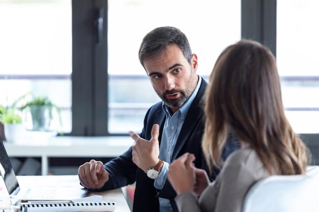 Strzał skoncentrowany młody biznesmen rozmawia ze swoim partnerem i robi notatki na temat przestrzeni coworkingowej.